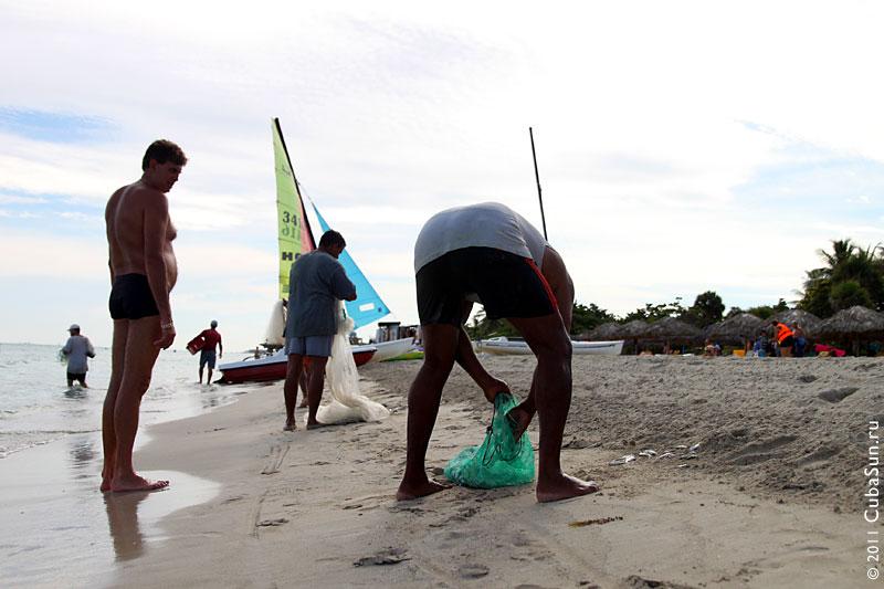 Рыбак вытрясает улов из сети.