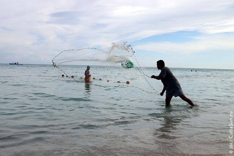 Рыбак забрасывает сеть в Атлантический океан на пляже Варадеро.